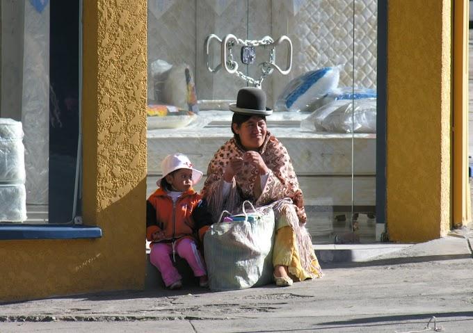 Mujer de pollera y su hija pequeña descansando