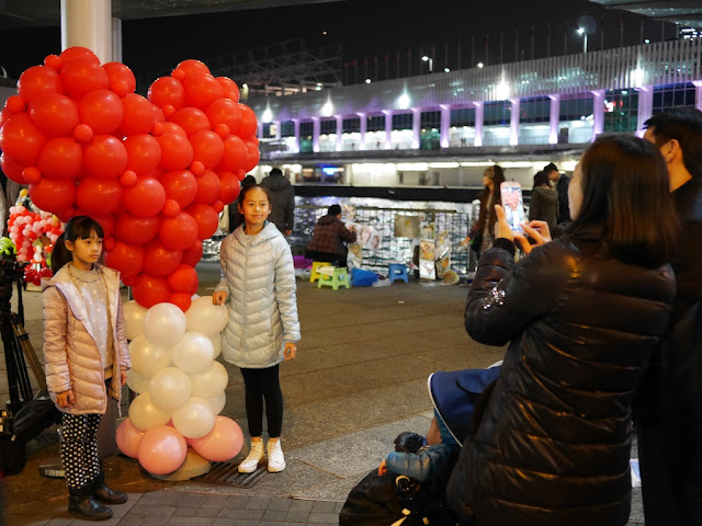 two girls posing for a photo next to a heart balloon sculpture
