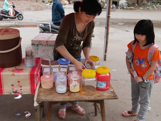 young girl waits as a woman makes milk tea on a small wooden table