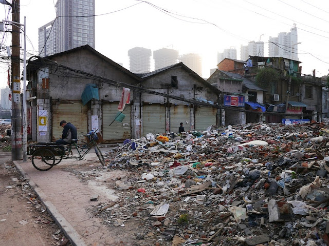 man resting while sitting on a tricycle cart parked next to demolished buildings at Beizheng Street in Changsha