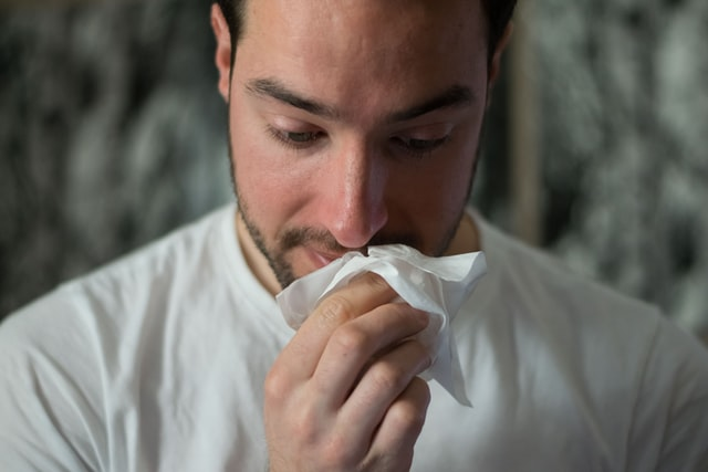 man using a tissue to wipe his nose.