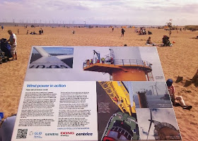 Skegness Beach Info board with turbines in sea on horizon
