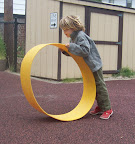 Child explores and experiences motion while using a large wide hoop to roll on and in.