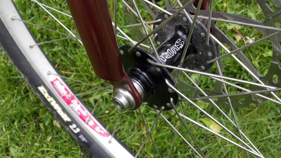 Downward, close up view of a black Surly Ultra New bike hub, installed in the front wheel of a brown bike - grass behind