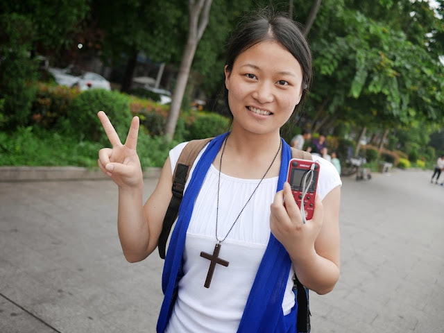 young woman holding a small electronic dictionary and wear a necklace with a cross