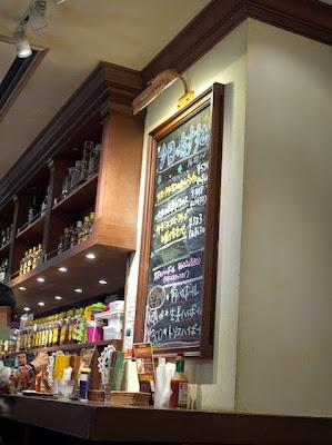 店内のウイスキーのボトル棚と黒板の案内