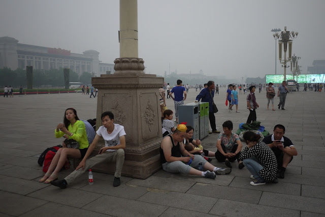 people sitting on the ground around a lamp post at Tiananmen Square
