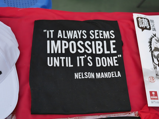 "shirt with Nelson Mandela's quote ""It always seems impossible until it's done"""