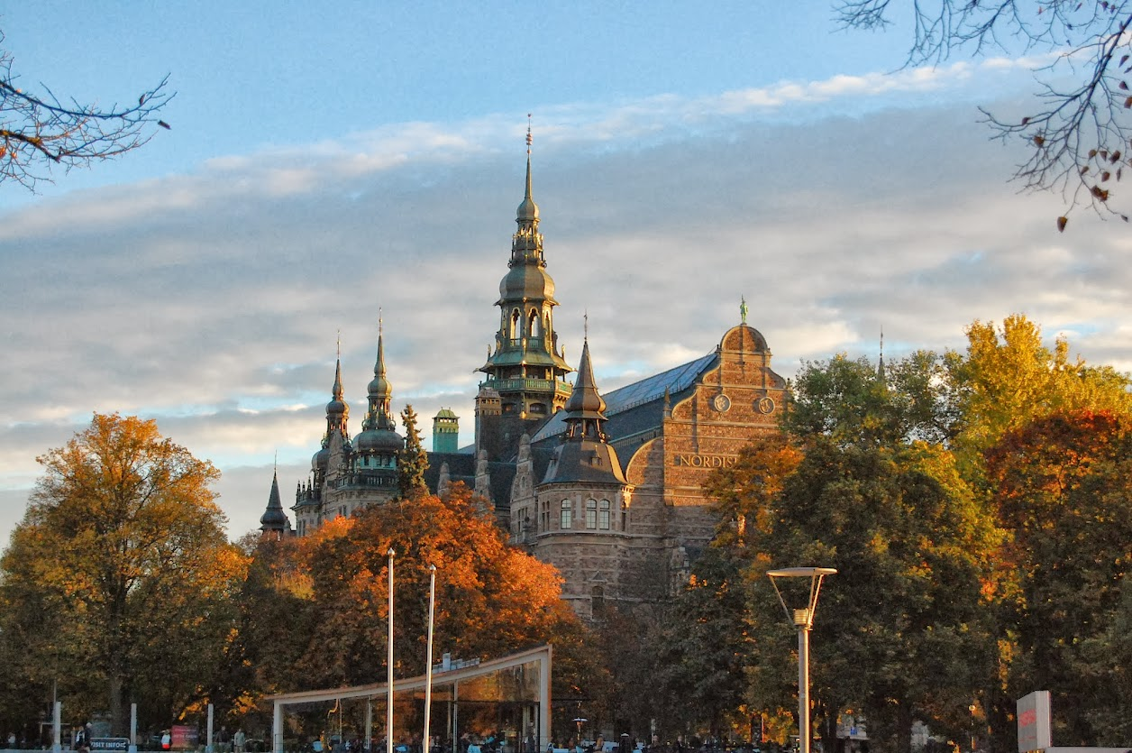 The spires of the Nordisk museum against a cloudy sky in fall foliage