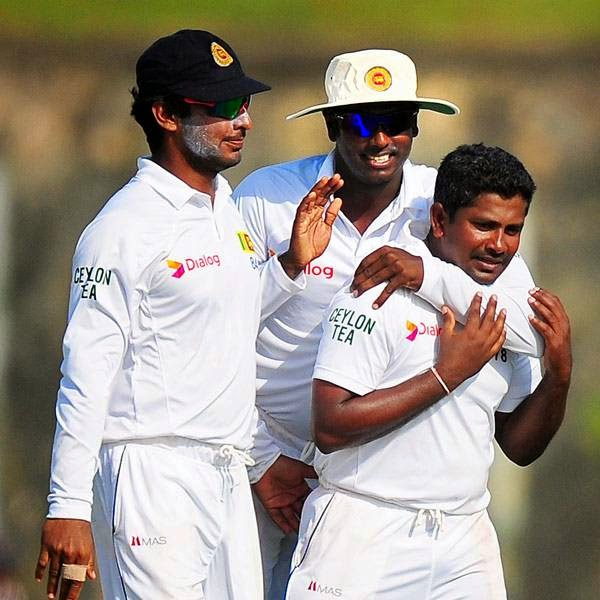 Sri Lankan cricketer Rangana Herath (R) celebrates with teammates Angelo Mathews (C) and Kumar Sangakkara (L) after Herath dismissed South Africa cricket captain Hashim Amla during the first day of the opening Test match between Sri Lanka and South Africa at the Galle International Cricket Stadium in Galle on July 16, 2014.