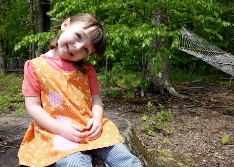 Made with Moxie:Roly-Poly Pinafore pattern review. Smiling girl sitting in the woods wearing Roly-Poly Pinafore.