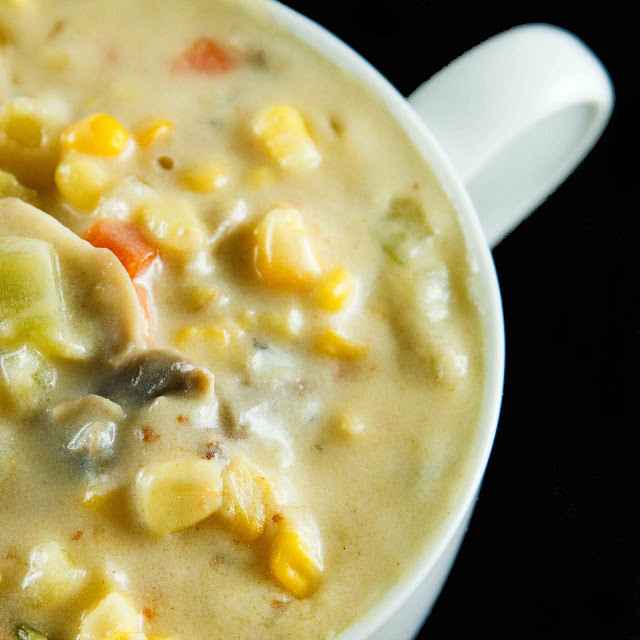 partial view of corn chowder in a large white soup mug