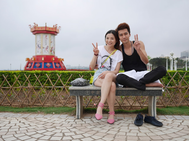 a young man and woman sitting on a bench at a park in Zhanjiang