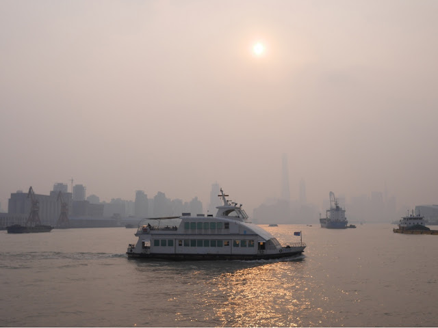 ferry crossing the Huangpu River on a smoggy day in Shanghai.