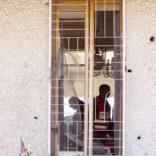 Soldiers of the Israeli Home Front Command through a smashed window during the clean-up operation at a home damaged in a missile strike in the southern Israel town of Ashdod.
