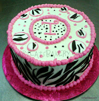 Pink and white butter cream girl's animal print creative birthday cake with black fondant zebra stripes and monogram