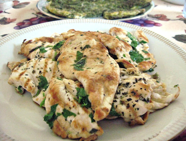 grilled chicken <pollo alla griglia> breast with parsley, lemon juice, extra virgin olive oil, red wine vinegar, and dried oregano.  Note the dish in the background is a asparagus frittata.