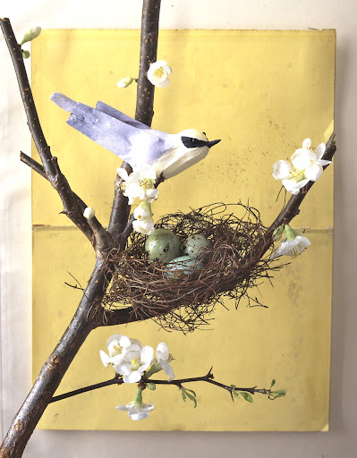 a detail of a paper bird, the eggs are quail eggs dyed with food coloring, and the nest is made with dried grape vine
