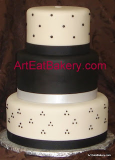 Three tier custom designed black and white fondant round wedding cake with swiss dots and ribbons