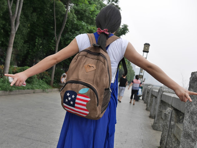 the young woman's backpack with a US flag colored Apple logo
