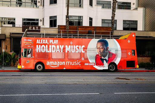 """A bus-side ad for Amazon Music with a picture of John Legend and message """"Alexa, play holiday music""""."""