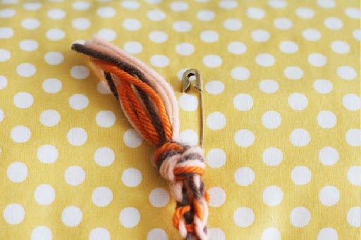 3. Tie the loose ends together with a knot and leave a tail of 2 inches. Safety pin to a pillow.