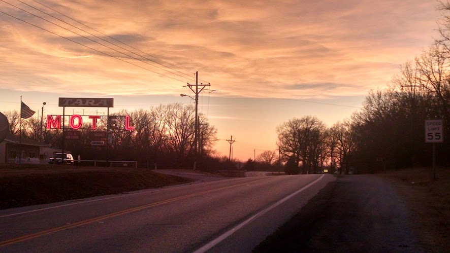 sunset behind neon motel sign and curving road