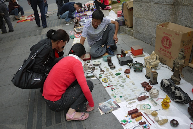 women squatting while looking at items on the ground for sale outside Tianxinge Antique City in Changsha, China