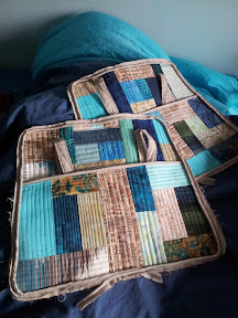 Two bag side pieces, each with large pocket across whole width, and quilted handles attached.