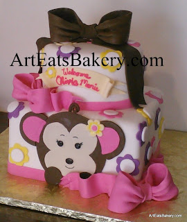 Three tier round and square creative monkey girl's baby shower cake design with yellow, purple and pink flowers and bows
