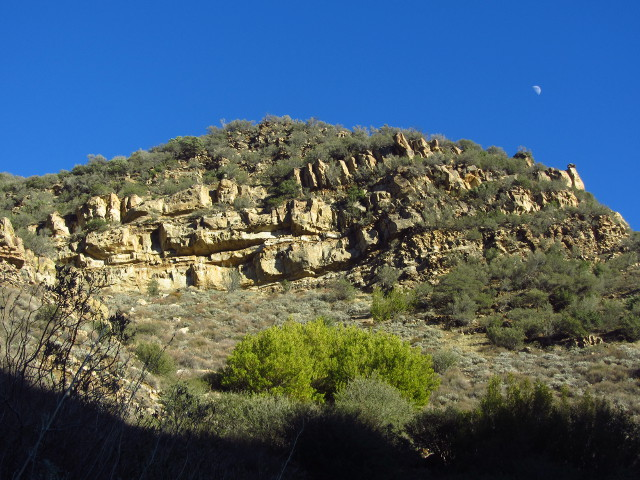 the moon above some horizontal layers of rock