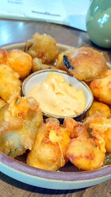 The Rookery at Raven & Rose has a food menu that includes fried cheese curds & fried pickles served with a smoked chili aioli.