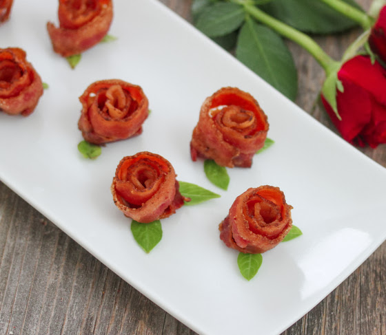bacon roses lined up on a serving plate
