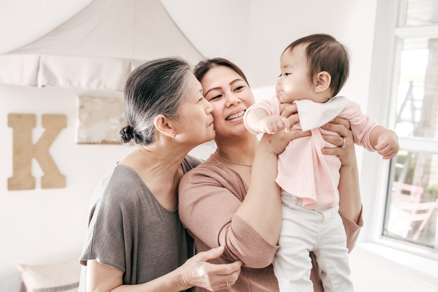 a woman holding up a baby girl while the woman's mother gives her a kiss on her cheek