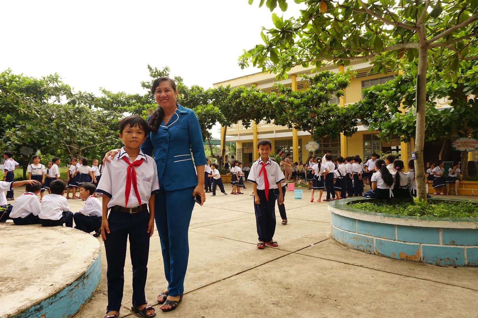 Cô giáo ân cần chụp hình cùng học sinh của mình, cô rất thương các cháu