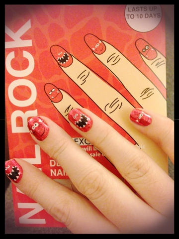 A picture of nails with red dinosaur faces on them
