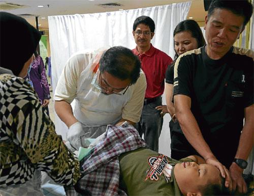 BERI SEMANGAT... Wai Hoong (kanan) memberi kata-kata semangat kepada Jun Hau ketika kanak-kanak itu dikhatankan oleh Dr Shahrizal