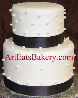 Two tier whtie fondant wedding cake with sugar pearls and black ribbons