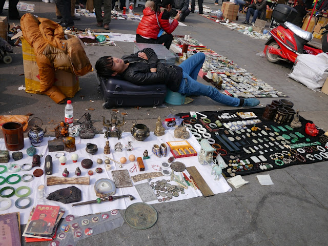 seller sleeping at an outdoor antique market in Changsha, China