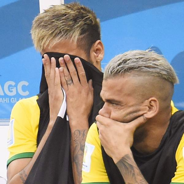 Brazil's injured forward Neymar (L) and defender Dani Alves react on the bench during the third place play-off football match between Brazil and Netherlands during the 2014 FIFA World Cup at the National Stadium in Brasilia on July 12, 2014.
