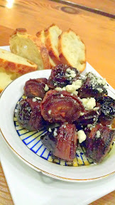 Oso Market + Bar appetizer of Tails & Trotters Chorizo-Stuffed Dates Wrapped in Bacon w/ Cumin Honey & Sage Oil