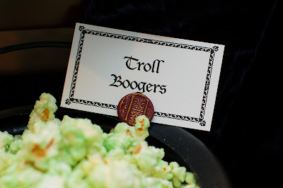 "Green chocolate covered popcorn in a black container with a sign that says ""Troll Boogers."""