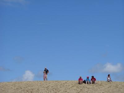 砂丘のてっぺんに並んで座る人々