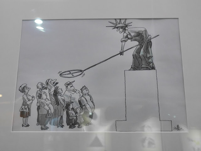 Security (安全) by Fang Tang (方唐) depicting the Statue of Liberty waving a metal detector over people
