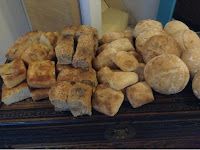 Focaccia, Wholemeal rolls, ciabatta & Cobb loaves laid out on a wooden chest