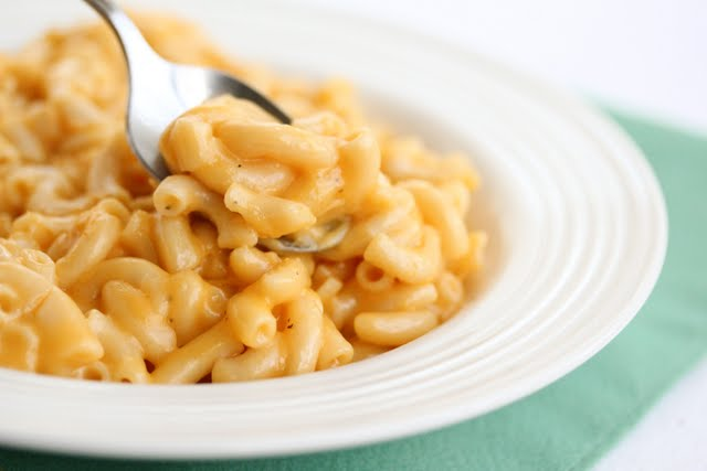 close-up photo of a spoon dipping into a bowl of macaroni and cheese