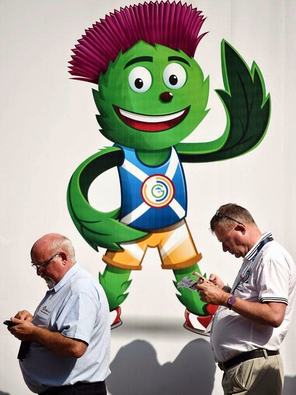 People queue to buy tickets for the 2014 Commonwealth Games in front of an image of the games' mascot Clyde Thistle in Glasgow on July 22, 2014, ahead of the start of the 2014 Commonwealth Games which begin on July 23, 2014.
