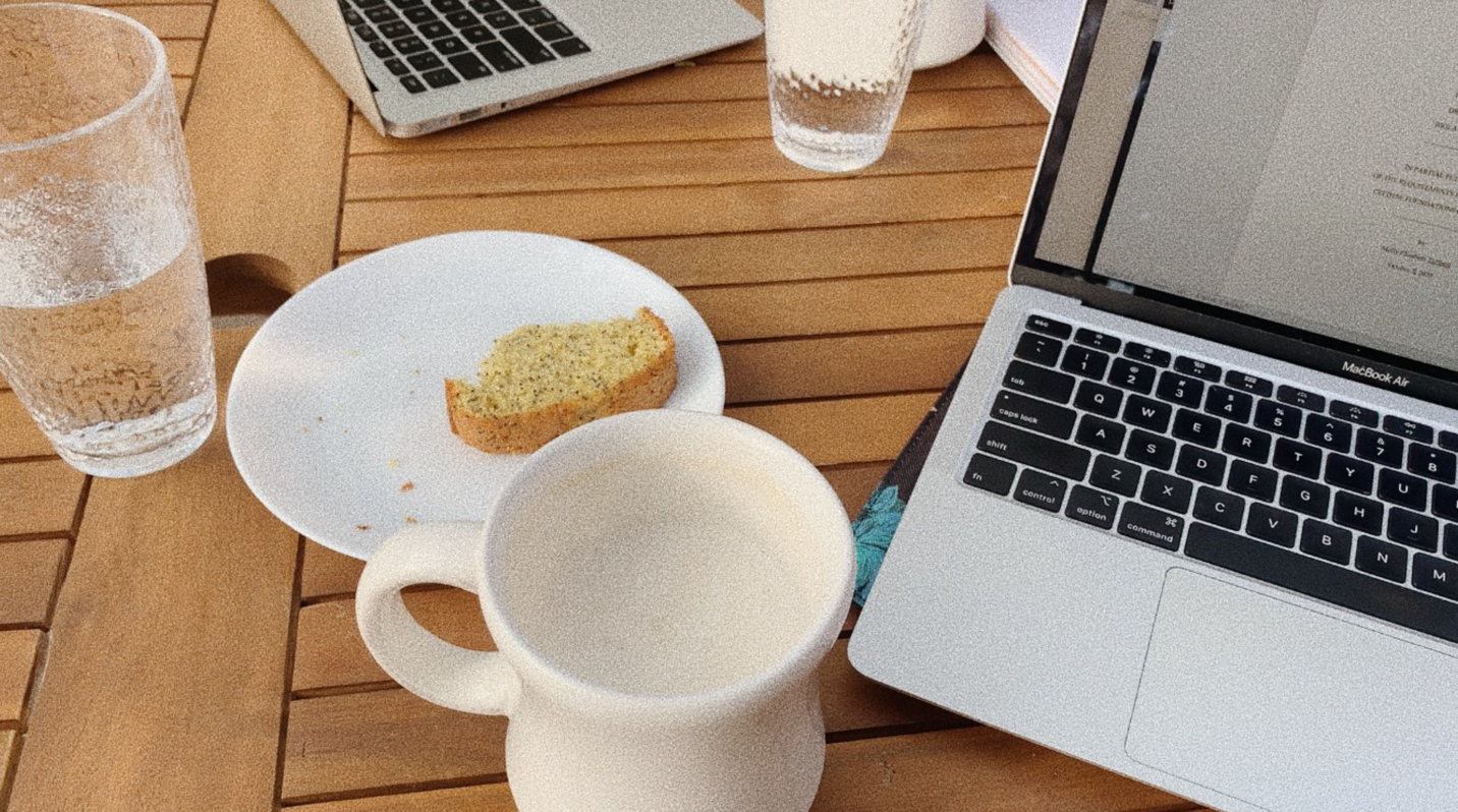 Molly's momentary desk: There's a glass of water, a cup of warm chai latte, a half-eaten slice of poppy seed bread on a white textured plate with a Macbook open towards the viewer of the photo