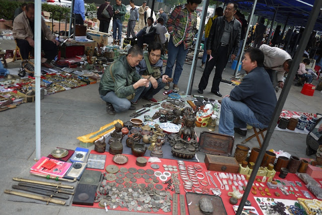 men squatting while examining a sword for sale outside Tianxinge Antique City in Changsha, China