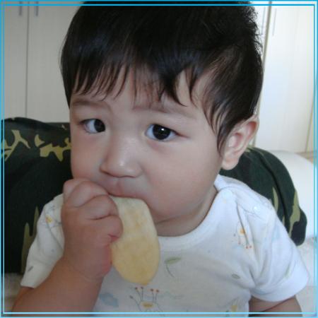 寶貝小輔自己拿著餅干嗑